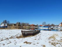 Homes and ships in river Minija in winter , Lithuania Stock Photos