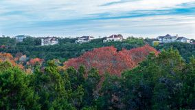 Homes on top of forest hill with fall colored trees. Homes on top of a forest hill with fall colored trees royalty free stock images