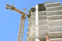 Homes under construction, moving crane over unfinished house Royalty Free Stock Image