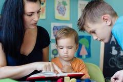 homeschooling她的孩子的母亲 库存图片