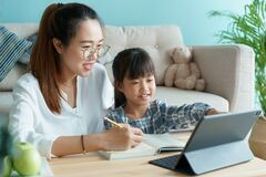 Free Homeschooling. Asian Family With Daughter Doing Homework By Using Tablet With Mother Help. Asia Mom And Child Learning Online With Stock Images - 192407424