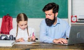 Homeschooling avec le père Ami de découverte pour vous aider à étudier Le?on priv?e Maître d'école et écolière avec l'ordinateur  photos stock