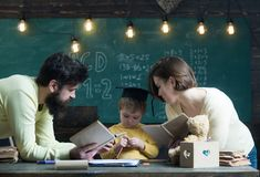 Homeschooling begrepp Fader- och moderläseböcker som undervisar deras son, svart tavla på bakgrund Familjen att bry sig omkring Royaltyfria Foton