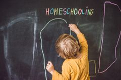 Homeschooling. The boy is drawing under word Homeschooling on a Royalty Free Stock Photos