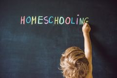 Homeschooling. Child pointing at word Homeschooling on a blackbo Stock Image