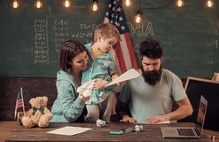 Homeschooling concept. American family at desk with son making paper planes. Kid with parents in classroom with usa flag. Chalkboard on background. Parents royalty free stock images
