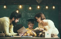 Homeschooling concept. Father and mother reading books, teaching their son, chalkboard on background. Family cares about stock photo