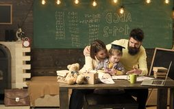 Homeschooling concept. Parents teaches son, chalkboard on background. Boy listening to mom and dad with attention royalty free stock photography