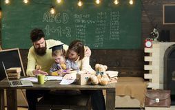 Homeschooling concept. Parents teaches son, chalkboard on background. Boy listening to mom and dad with attention royalty free stock photos