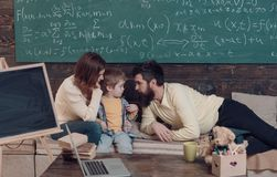 Homeschooling concept. Parents teaching kid, speaking. Boy listening to mom and dad with attention. Parents teaches son royalty free stock photo