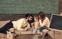 Homeschooling concept. Parents teaching kid, speaking. Boy listening to mom and dad with attention. Parents teaches son stock photos