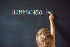 homeschooling Dziecko wskazuje przy słowem Homeschooling na blackbo obraz stock