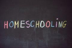 homeschooling Kind, das auf Wort Homeschooling auf einem blackbo zeigt lizenzfreies stockfoto