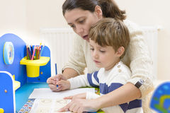 Homeschooling. Mother helping her kid to make drawings Royalty Free Stock Image
