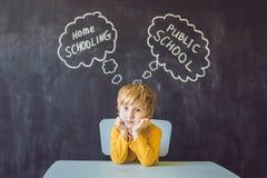 Homeschooling vs kommunala skolor - pojken sitter på tabellen och Arkivfoton