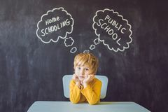 Homeschooling vs Public Schools - The boy sits at the table and Stock Photos