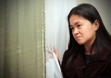 Homesick. An adult woman looking out the window with an expression of sadness or longing Royalty Free Stock Image