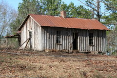 Homestead. Old farm shack with tin roof and brick chimney Royalty Free Stock Photos
