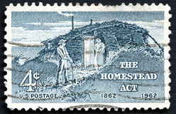 The Homestead Act US Postage Stamp. UNITED STATES OF AMERICA - CIRCA 1962: A used US postage stamp commemorating the 100th Anniversary since the 1862 Homestead Royalty Free Stock Photography