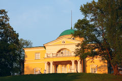 Homestead in the classical style. Manor house in the classical style on a hilltop surrounded by park. In the rays of setting sun Stock Photos