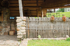 Homestead house and wicker fence with old pots Stock Photos