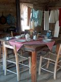 Homestead Kitchen. An old single room homestead.  The table is ready for a meal alongside drying clothes Stock Image