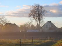 Homestead in morning mist, Lithuania royalty free stock image