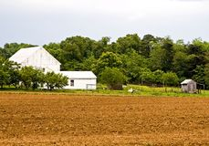 Homestead with Plowed Field. Storm approaches an old farm homestead just as plowing of the field is completed for spring planting stock images