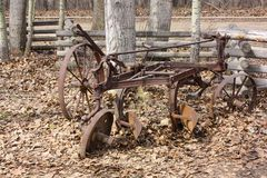 Homestead scene of abandoned antique iron plow. royalty free stock image
