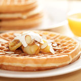 Homestyle waffles. Homemade waffles with caramel glazed apples, cream and sliced almonds Royalty Free Stock Image