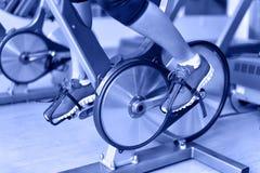 Hometrainer met spinnewielen - vrouw het biking Stock Afbeelding