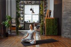 homeware实践的平衡瑜伽姿势的少妇在地毯在她轻松的卧室 免版税库存图片