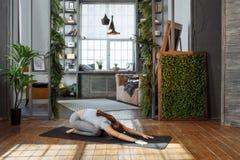 homeware实践的平衡瑜伽姿势的少妇在地毯在她轻松的卧室 免版税库存照片