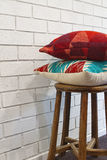 Homewares decorator cushions on a wooden stool Royalty Free Stock Photos