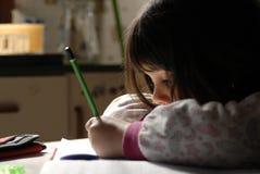 Homework. A small girl doing her homework royalty free stock image