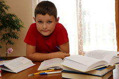 Homework. 8 years old child reading book and doing his homework Royalty Free Stock Images