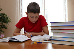 Homework. 8 years old child reading book and doing his homework Stock Image
