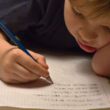 Homework. Child  rests his head on the table while doing his homework in russian writing Stock Photography