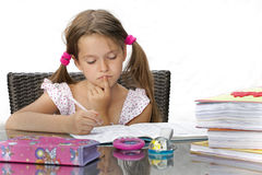 Homework. 7 year old girl at the table with homework Stock Photography