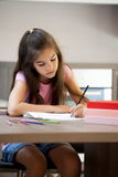 Homework. Little girl concentrated while doing her homework Royalty Free Stock Image