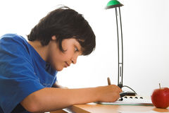 Homework. Boy doing his homework on his desk stock photo