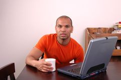 Homework. A young man has coffee while doing homework on his laptop Stock Photo
