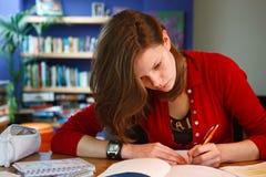 Homework. Young female student doing her homework. Shallow dof ,focus on eye Stock Photography