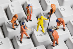 Homework. Stock photo of worker figurines posed around the Home key on a computer keyboard Stock Image