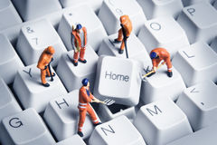 Homework. Worker figurines posed around the Home key on a computer keyboard Royalty Free Stock Photos