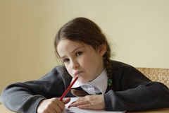 Homework. Pretty girl thinking about what to write next Royalty Free Stock Images