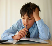 Homework again !. Schoolboy doing his studies, white background Stock Photo