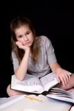 Homework Blues. Middle school girl overwhelmed or bored by homework, surrounded by opened text books Stock Photo