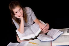 Homework Blues. Middle school girl overwhelmed or bored by homework, surrounded by opened text books Stock Image