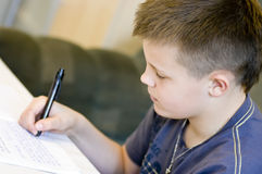Homework boy. A teenage boy doing his homework, writing in his notebook stock image